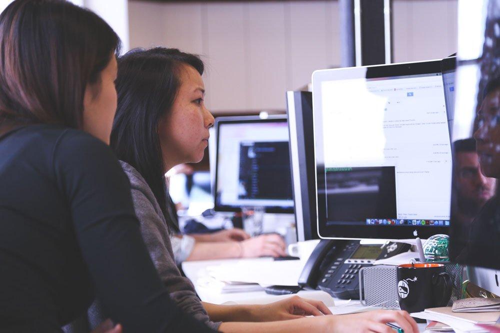 Women Analyzing Data on Desktop