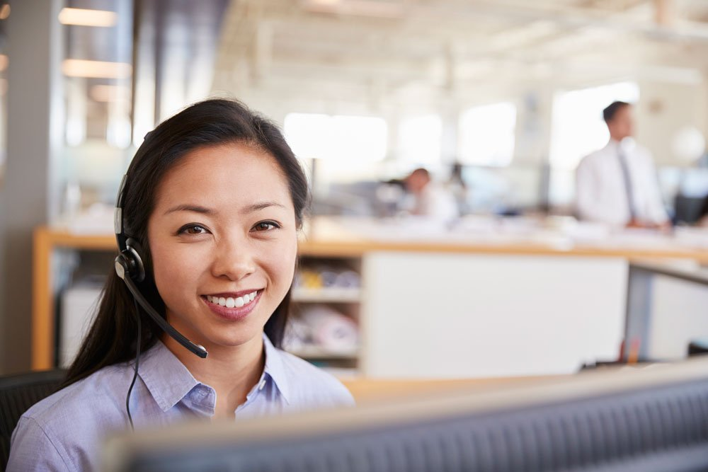 young asian woman working in a call centre smiling